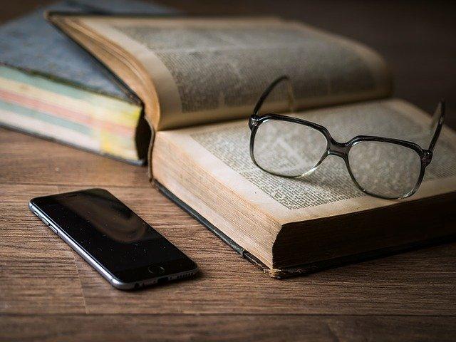 brýle a telefon u knihy