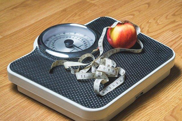 váha s krejčovským metrem a jablkem