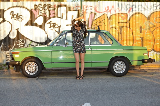 žena opírající se o zaparkované auto