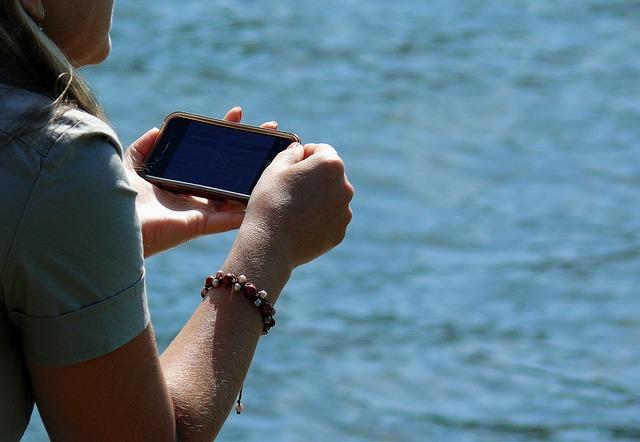 člověk sedící u vody s mobilem v ruce
