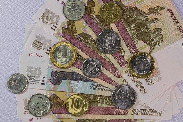 vějíř bankovek posetý mincemi.jpg