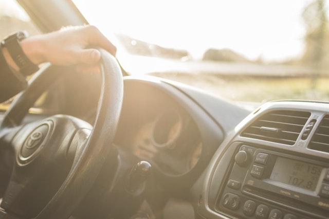 automobil uvnitř, volant, který někdo drží, rádio a světlo venku