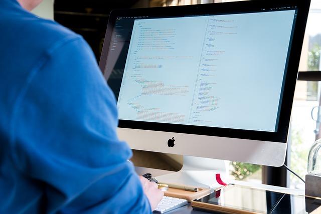 Muž sledující data na monitoru PC