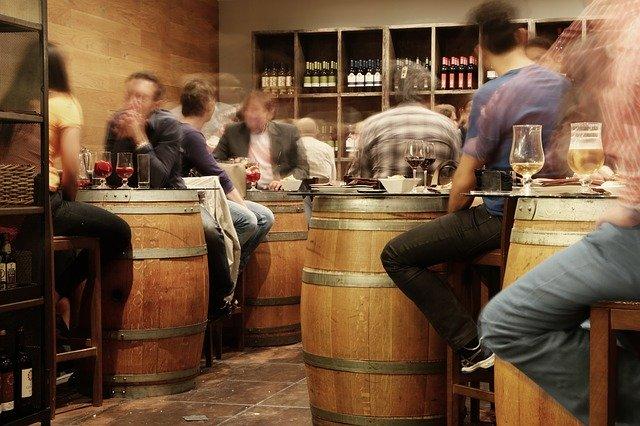 hosti sedící u dubových soudků – stolů v hospodě